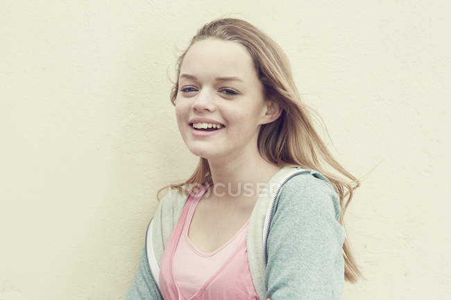 Portrait of smiling girl with long blond hair in front of wall — Stock Photo