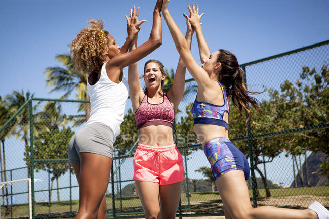 Three women, on outdoor sports court, jumping and giving high fives — Stock Photo