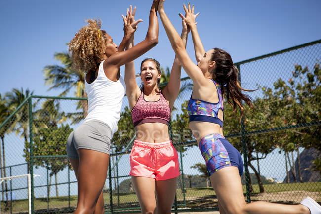 Три женщины, на открытый спортивный корт, прыжки и давая высокого пятерки — стоковое фото