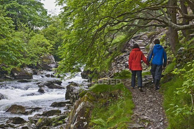 Couples sur le chemin de bord de la rivière à côté de la rivière Aberglaslyn, Pont Aberglaslyn, Caernarfon, Gwynedd, Pays de Galles du Nord, Royaume-Uni — Photo de stock