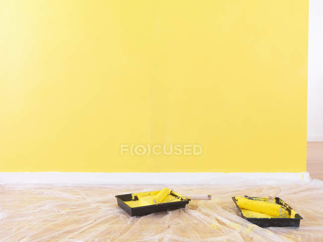 Валики малярські на підлозі поруч жовті пофарбованих стіни — стокове фото