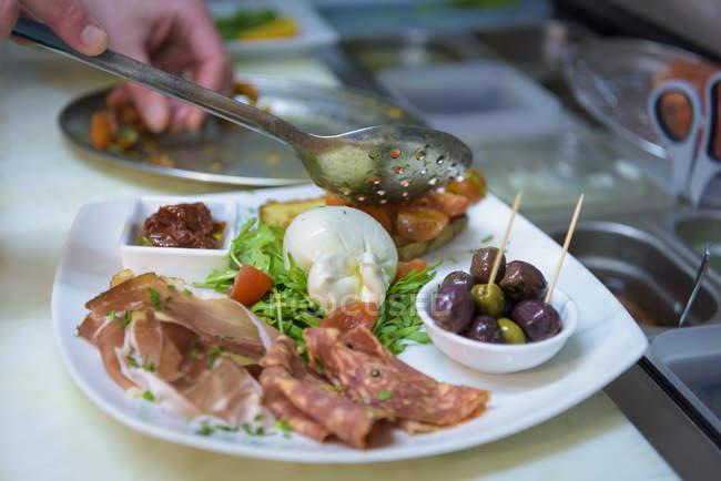Chef preparing antipasti in traditional Italian restaurant kitchen, close up — Stock Photo