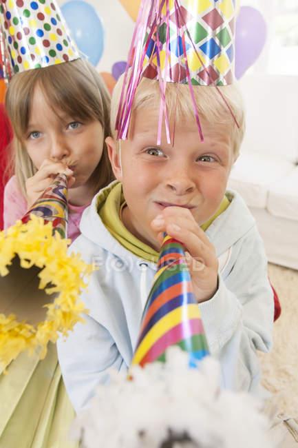 Хлопчик і дівчинка дивляться на камеру, що випускає гудзики — стокове фото