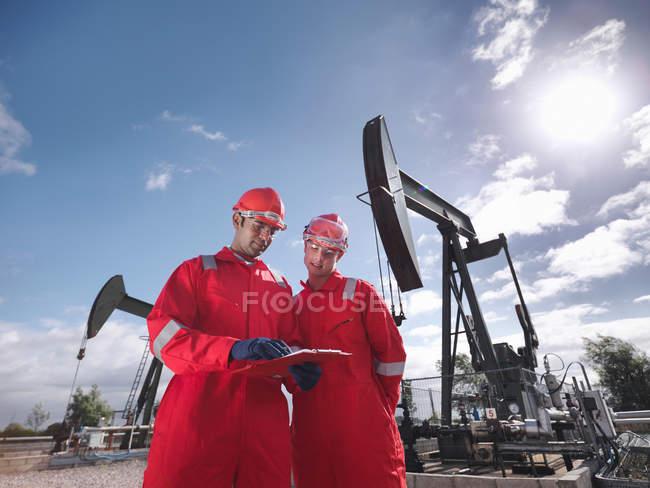 Deux travailleurs regardant un presse-papiers, devant des pompes à huile au-dessus de puits de pétrole terrestres (hochant la tête à des ânes / pompiers ) — Photo de stock