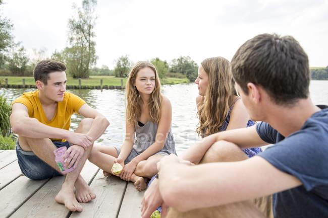 Группа молодых людей, сидящих на причале, расслабляется — стоковое фото