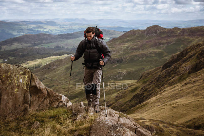 Young male hiker moving up mountain, The Lake District, Cumbria, UK - foto de stock