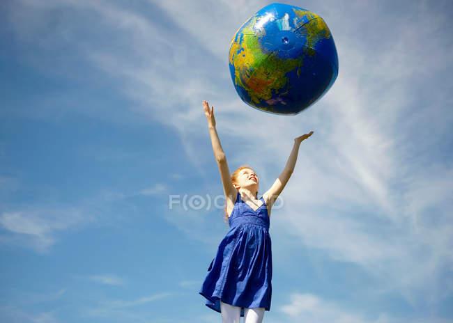 Молодая девушка бросает надувной глобус — стоковое фото