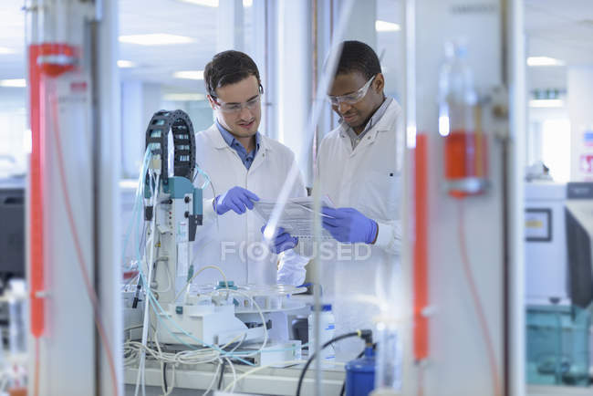 Scientists inspecting coloured samples in testing laboratory — Stock Photo