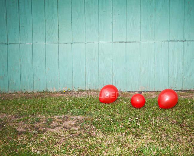 Palloncini rossi sull'erba contro la parete azzurra — Foto stock