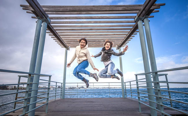 Two young female friends jumping in unison on sea pier — Stock Photo