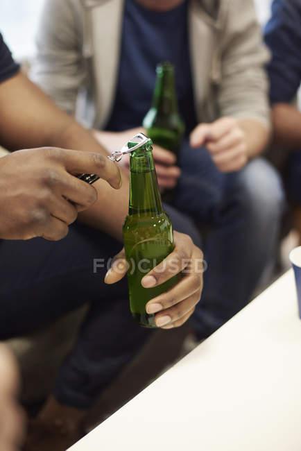 Обрізаний вид mans руки відкриття пляшку пива — стокове фото