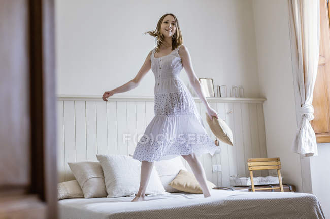 Young woman in long white dress jumping on bed looking at camera smiling — Stock Photo