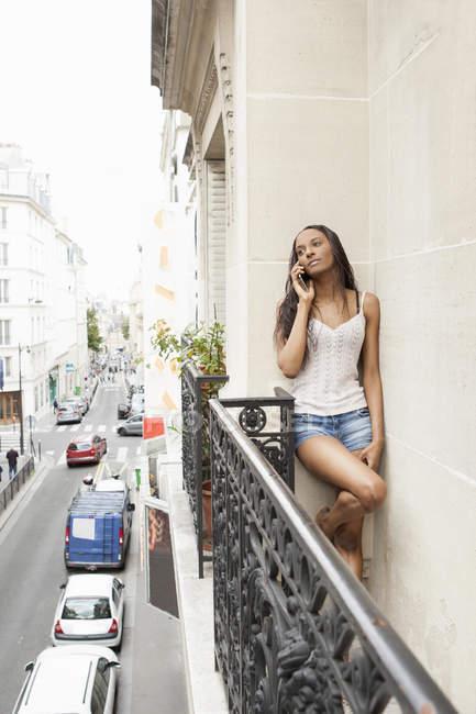 Mujer con teléfono en el balcón, París, Francia - foto de stock