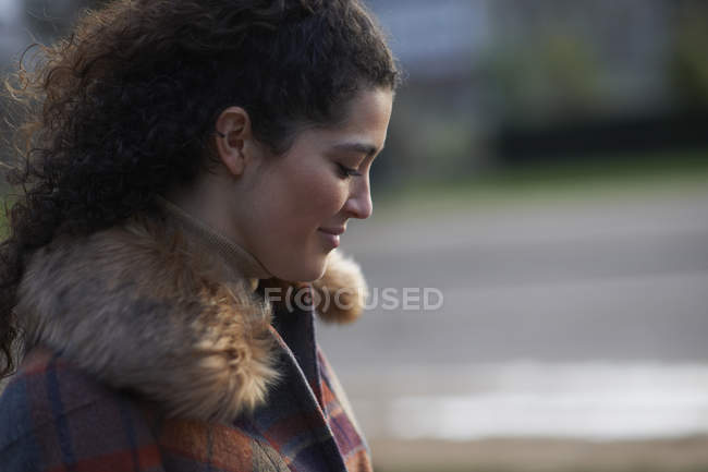 Side view of curly haired woman wearing tartan fur trim coat looking down smiling — Stock Photo