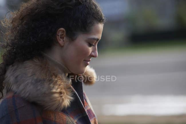 Vista laterale della donna dai capelli riccia indossa cappotto tartan pelliccia trim in guardando giù sorridente — Foto stock