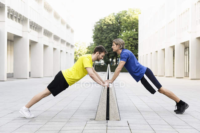 Men stretching on divider in alley between office buildings — Stock Photo