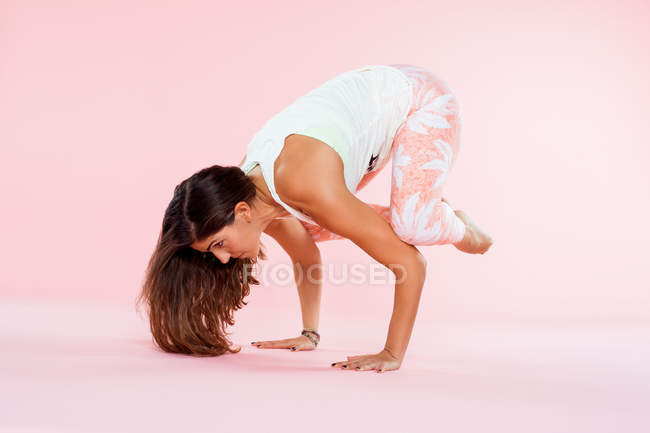 Studio shot of young woman in yoga position balancing with hands on floor and knees on elbows — Stock Photo