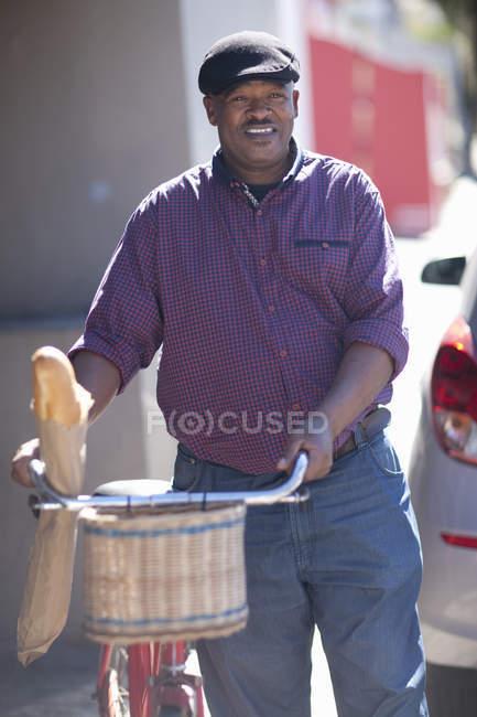 Старший велосипедист с багетом в велосипедной корзине — стоковое фото