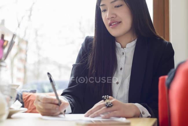 Портрет жінка написання на папері на стіл — стокове фото