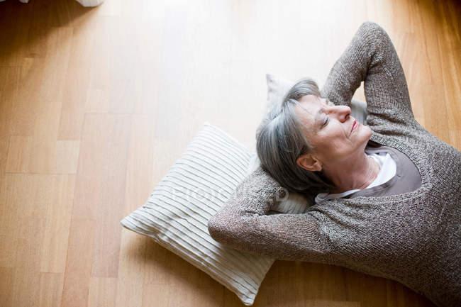 Vecchia donna rilassante sul pavimento — Foto stock