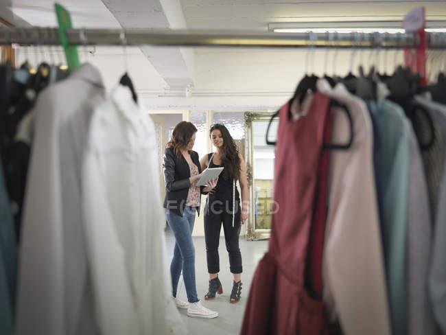 Fashion designers using digital tablet in fashion design studio — стокове фото