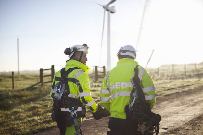 Two engineers at wind farm walking together, rear view — Foto stock