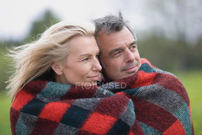 Coppia in coperta guardando altrove — Foto stock
