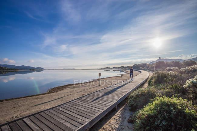 Young female runner running along beach boardwalk, Villasimius, Sardinia, Italy — Stock Photo