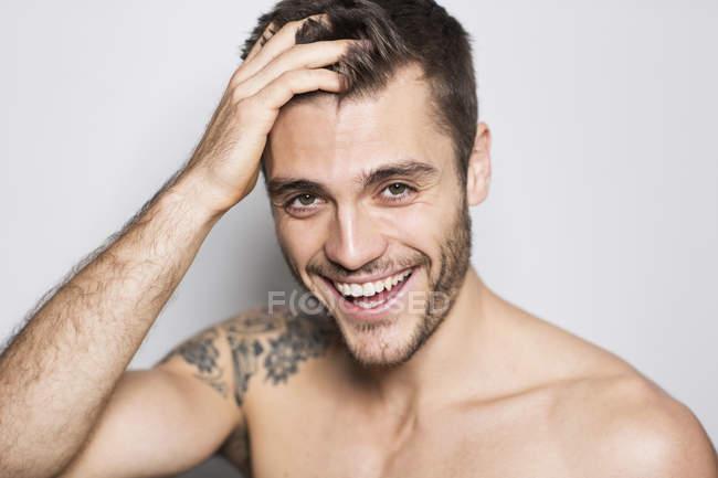 Retrato de jovem sorridente com tatuagem no ombro — Fotografia de Stock