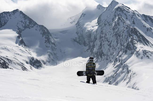 Молодой сноубордист-мужчина, идущий на гору, Обергургль, Австрия — стоковое фото