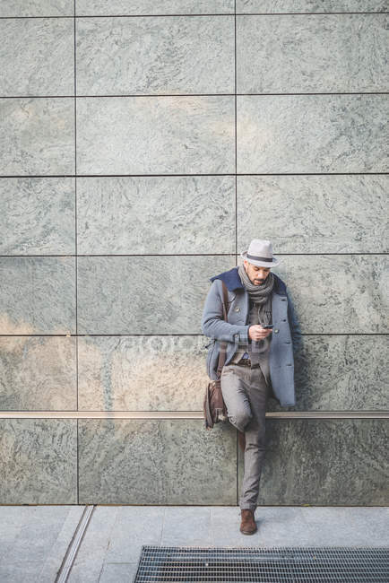 Businessman leaning against wall texting on smartphone — Stock Photo