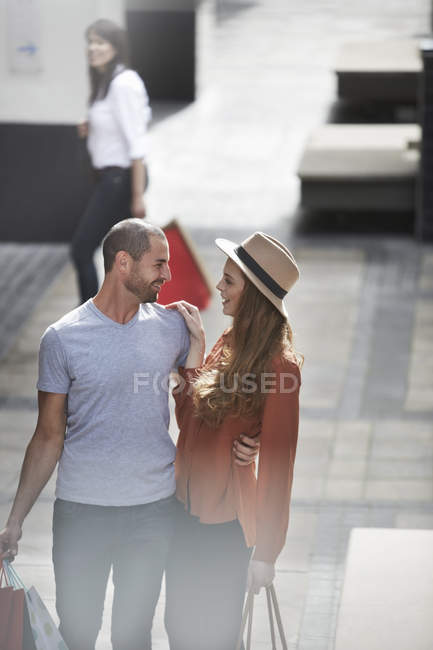 Couple in shopping mall, standing face to face, holding shopping bags — Stock Photo
