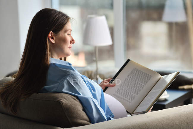 Pregnant woman sitting on sofa, reading book — Stock Photo