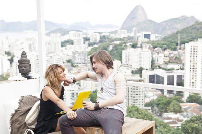 Young couple using laptop on rooftop terrace, Rio De Janeiro, Brazil — Stock Photo