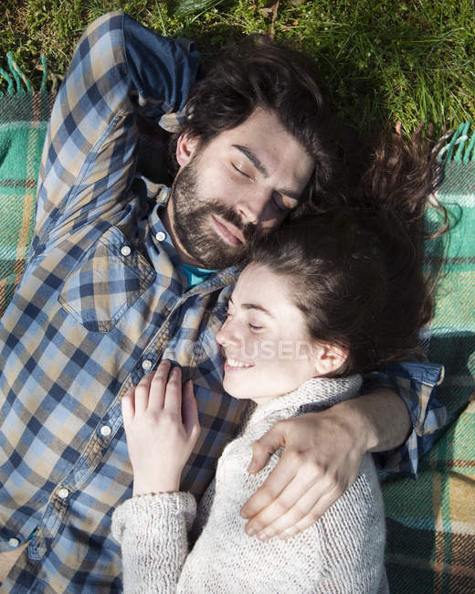 Young couple lying with closed eyes on picnic blanket — Fotografia de Stock