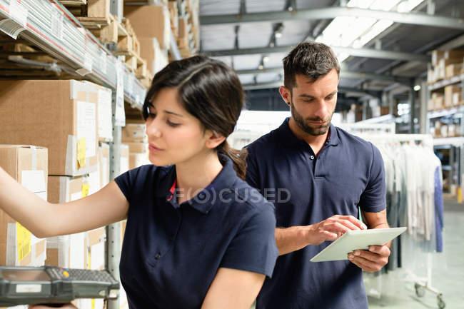 Trabajadores de las fábricas que utilizan tabletas digitales para preparar el orden en el almacén de distribución - foto de stock