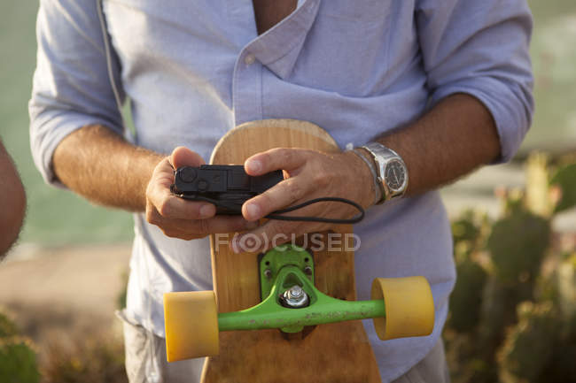 Mann hält Kamera und Skateboard in der Hand, Schnappschuss — Stockfoto