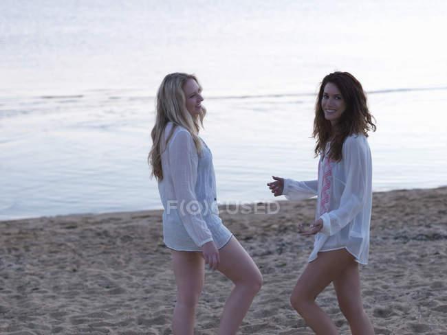 Two young women standing on beach at dusk — Fotografia de Stock