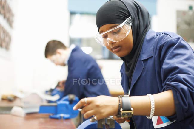 Estudiante femenina usando antivicio en taller universitario - foto de stock