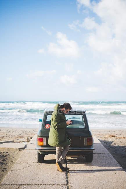 Мужчина с винтажной машиной, припаркованный на пляже, читает смс смартфоны, Сорсо, Сассари, Сардиния, Италия — стоковое фото