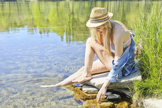 Young woman sitting on rocks by water — Stock Photo