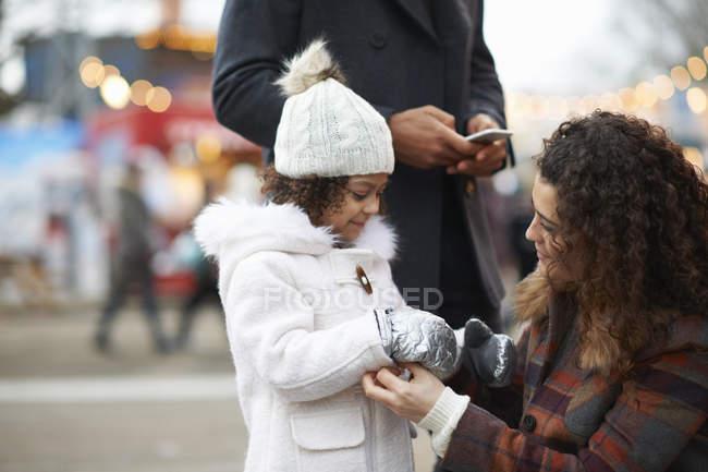 Mãe agachamento ajudando filha colocar mitenes — Fotografia de Stock