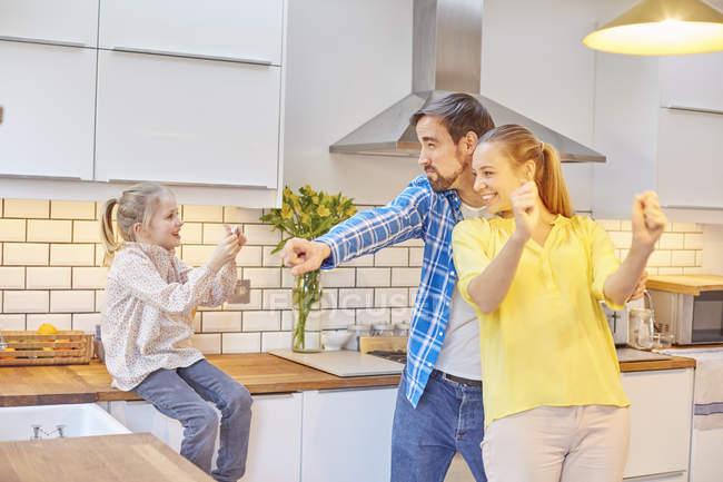 Hija tomando fotos de padres divertidos en la cocina - foto de stock