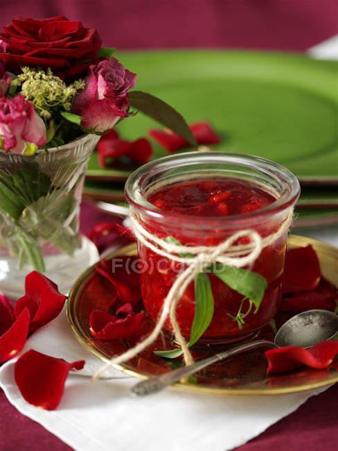 Glas hausgemachte Johannisbeermarmelade und Rosenblätter auf dem Tisch — Stockfoto