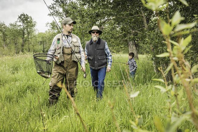 Multi familia de generación en campo llevando Cañas y red de pesca - foto de stock