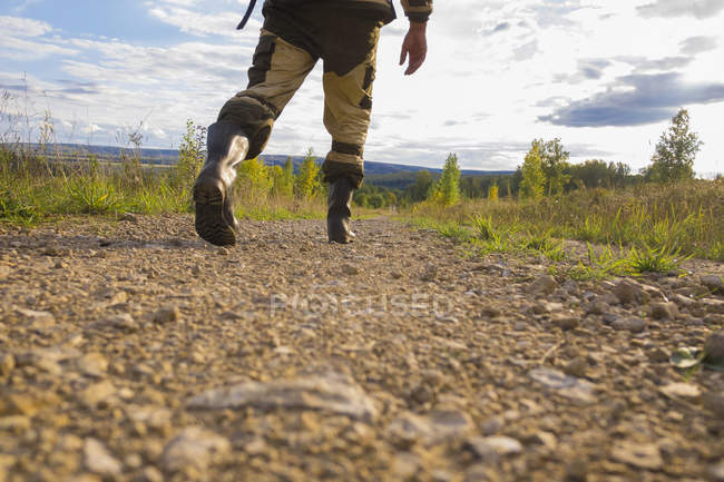Mid adult man walking on dirt path, low section — Stock Photo