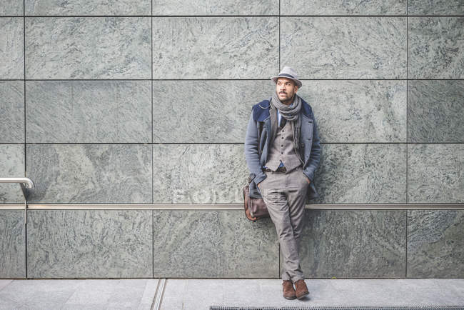 Portrait of businessman leaning against wall — Stock Photo