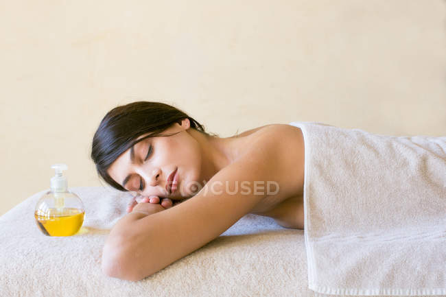 Young woman with eyes closed lying on treatment couch at spa — Stock Photo