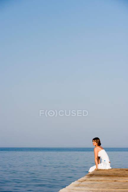 Femme assise sur une jetée à la mer — Photo de stock