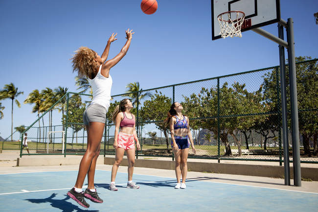 Young woman throwing basketball towards hoop while friends watch on — Stock Photo
